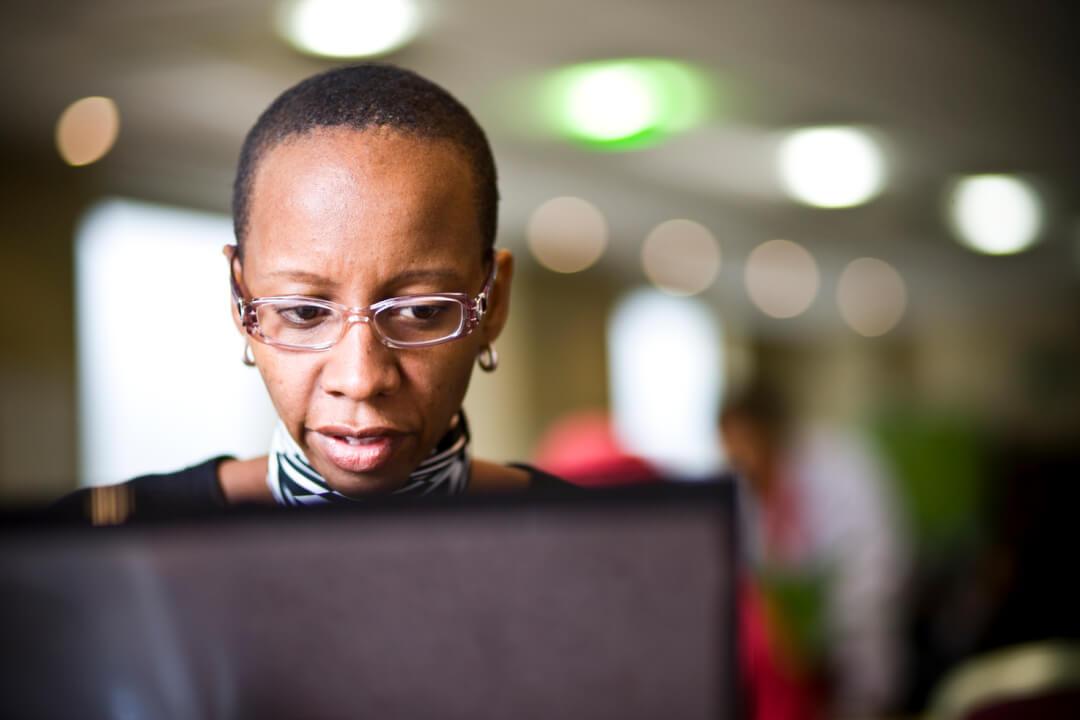 Uma mulher negra de óculos sentada utilizando um notebook. Fundo da imagem desfocado.
